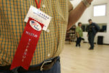 (BG960) Election supervisor Frank Lujan, 78, wears an Habla Espanol ribbon to let people know if...