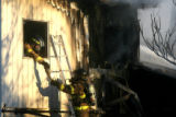 Firefighters hand off extra oxygen bottles while fighting  a house fire at 7820 Larkwood Street in...