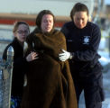 Cindy Trujillo (cq) ,center, is led away by a family friend (left, and a paramedic ,right)  from...