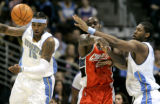 Denver Nuggets forward Carmelo Anthony knocks the ball loose from Charlotte Bobcat Emeka Okafor,...