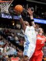 Denver Nuggets guard JR Smith, left, puts in a reverse lay-up being defended by Charlotte Bobcats...