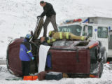 Rescue workers work to free a man from his rolled over vehicle on the median of I - 70 near...
