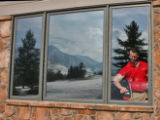 Greg Dean (cq), of Percision Films,  cleans a window before  putting a new solar film sheet on it,...