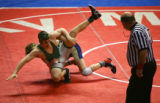 Mullen's Seamus Waples (in back in blue and yellow) takes down Delta's Luke Laurita (front in...