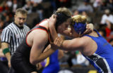 Florence's Jon Medley (right in blue) wrestles Scott Redden (left in black) during the Class 3A...