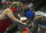 Montrose's Adrian Gallegos (left in red) grapples with Broomfield's Josiah Graham (right in grey)...