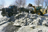 A front-end loader dumps ice and snow into a dumptruck near 10th Avenue and Jackson Street on...