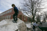 Niko Sandusky (cq),5, plays on a mound of snow as parents join together to break ice off of the...