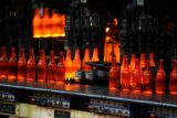 (DLM0642) -  Red-hot bottles come out of the forming machine at the Owens-Illinois glass bottle...