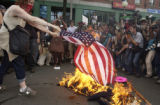 DNC04078PROTEST Boston, July 29, 2004 - A protester burns an American flag within sight of the...