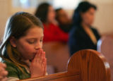 Anna Scheitler (cq), 7, prays at morning mass for Ash Wednesday at the Our Lady of Guadalupe...