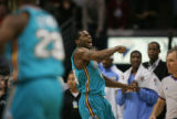 The Denver Nuggets bench watches on as the New Orleans Hornets' Desmond Mason (#24) reacts after...