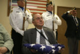 World War II veteran Ernest Peterson smile after being presented the American flag, Thursday Feb....