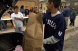 (BRIGHTON, Colo., May 12, 2004) Joseph Cedillo,13, loads a bag of donated food in the trunk of...