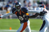(DOVE VALLEY, Co., SHOT 7/30/2004) Denver Broncos' wide receiver Rod Smith (#80) tries to slip the...