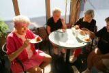 93-year-old Marion Downs (cq), left, eats her birthday cake with friends at the Meadow Creek...