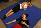 MJM431 Mariana Lima (cq), bottom, takes a break from stretching with fellow performer, Luana Costa...