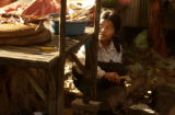 Kampong Chnang, Cambodia.  November 4, 2003.      Sixteen-year-old Leakhana Hi prepares a fire to...