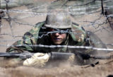 (COLORADO SPRINGS, Colorado. August 01, 2004) A  Basic Cadet makes his way under the  barbed wire...