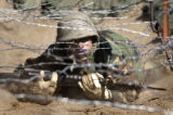 (COLORADO SPRINGS, Colorado. August 01, 2004) A  Basic Cadet makes her way under the  barbed wire...