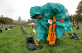 Vrnda Noel (cq Vrnda Noel) places flowers  Monday morning October 9, 2006 on boots from a list...