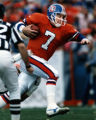 (DENVER, COLO., 1/14/90) Broncos quarterback John Elway fights for yardage against the Cleveland...