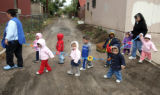 The Westside Daycare Center , out for a morning tour of the neighborhood , walk across the alley...