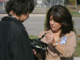 JPM349 - School supervisor Nancy Stark, right, examines a Army surplus gas mask around the neck of...