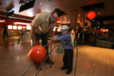 Colorado Avalanche hockey player Ken Klee, cq, helps Christian Howell, 4, of Castle Rock  bowl at...