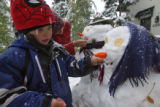 DLM00004   Kristan Laird, 5, puts the final touches on a snowwoman in the Park Hill neighborhood...