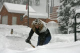 Eight year resident Connie Mandell (cq) works on clearing heavy wet snow from her driveway on...
