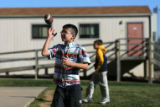 Alex Fernandez (cq), 10, of Littleton, plays with a ball as he walks past a mobile classroom at...