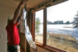Greg Dean (cq), of Percision Films, gets ready to put a new solar film sheet on a window, in a...