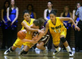 Regis University's Denise (#43, right) and Diana Lopez (#31, left) team up to try and force a...