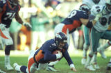 (DENVER, COLO., JANUARY 9, 1999) Broncos quarterback John Elway dives forward for as much yardage...