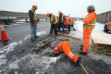 CDOT Foreman Alan Martinez (cq)  looks into a  giant pothole during repair work in the middle lane...