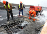 L to R: CDOT workers Ed Gentry (cq), Ron Bickerhoff (cq), and Foreman Alan Martinez (cq) repair a...