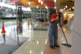 Phil O'Neal, cq, of PCL Construction, mops up excess sealant applied to the tile Monday Feb. 19,...