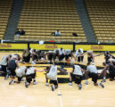 The University of Colorado's mens basketball team kneels in prayer at center court of the Coors...