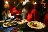 "Guests line up to decide which dishes they want to sample during a ""family-style"" meal..."