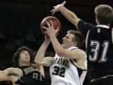 Arapahoe's Levi Knutson goes up for a shot being defended by Monarch's Mike Kawoluk, left, and...