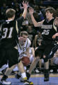 Arapahoe's Levi Knutson, middle, drives to the basket  being defended by Monarch's  Ryan Magiera,...