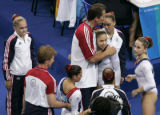 (ATHENS, GREECE, AUGUST 17, 2004)  USA's coach, Evegeny Marchanko hugs, Courtney Kupets after she...