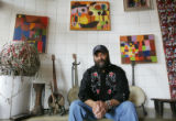 Blues musician Otis Taylor at his home in Boulder, with his father's paintings on the wall, and...