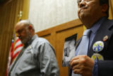 Rep. John Kefalas (right), D-Dist. 52, listens on as he holds up a photo of his granddaughter,...
