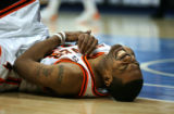 The Denver Nuggets' Marcus Camby (#23) grimaces while holding his arm after hitting the floor hard...