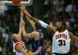 The Denver Nuggets' Steve Blake (#25, left) and Nene (#31, right) try to block the shot of the...