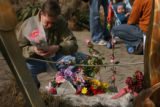 MJM375  Peter Smith rearranges a bundle of flowers that he brought Sunday to add to a makeshift...