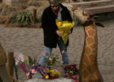 MJM381  Michelle Catlett (cq) lays down flowers at a makeshift memorial Sunday for a Zoo keeper,...