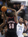 Denver Nuggets' center Marcus Camby, right, leaps to block a shot on the goal by Portland Trail...